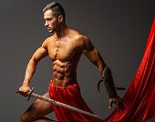 Muscular guy with sword on grey background
