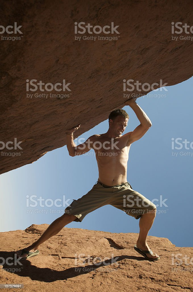 Shirtless Guy Lifts Huge Boulder into the Sky royalty-free stock photo