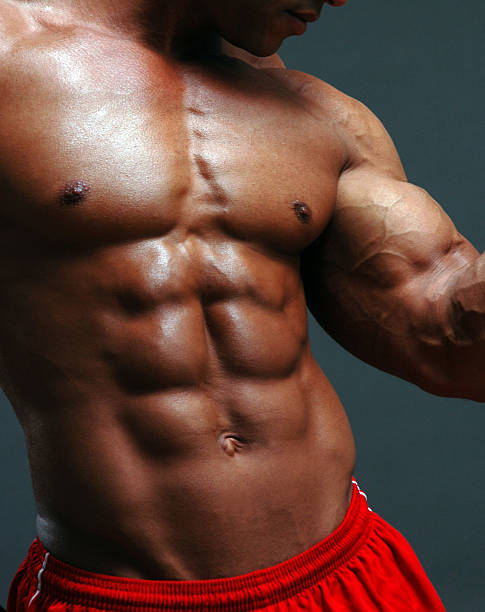 Shirtless male body builder flexes muscles stock photo