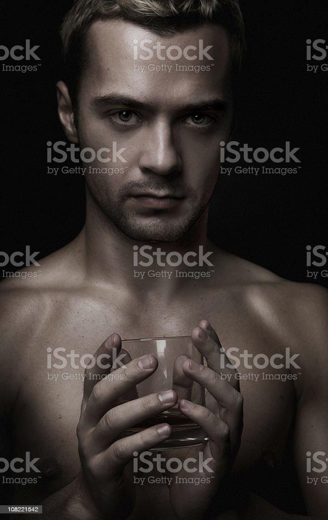 Shirtless Man Holding Glass of Whiskey royalty-free stock photo