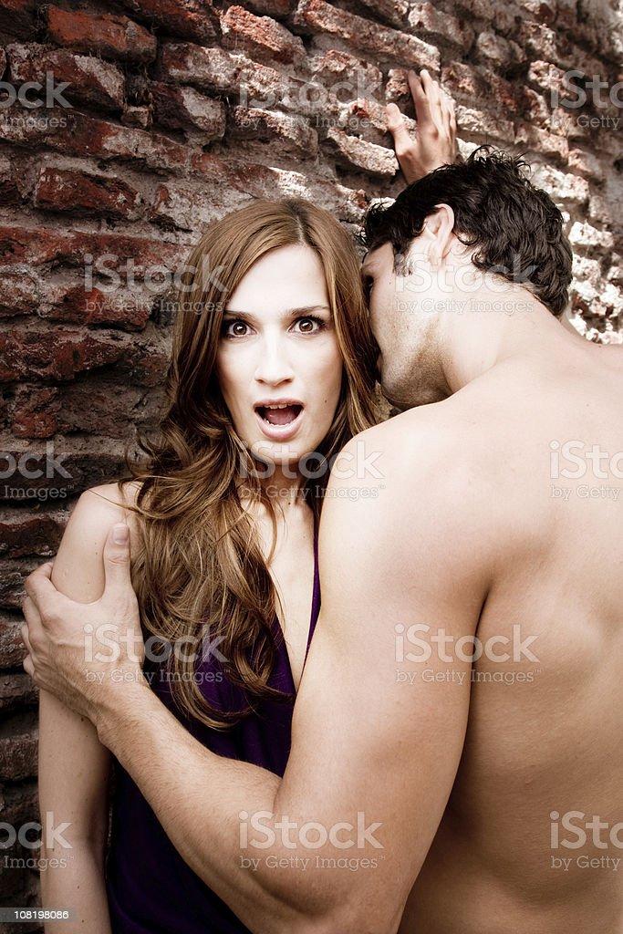 Shirtless Man Holding Surprised Woman Near Brick Wall royalty-free stock photo