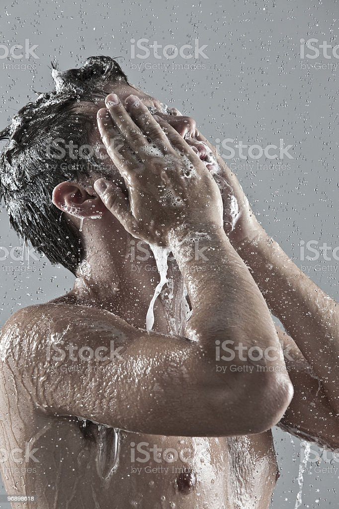 Shirtless man in the shower washing his face royalty-free stock photo