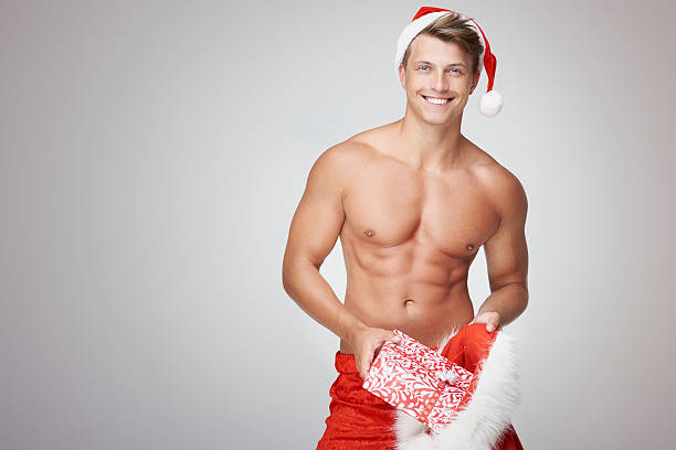 shirtless man inserting some christmas presents - naked santa claus stock pictures, royalty-free photos & images