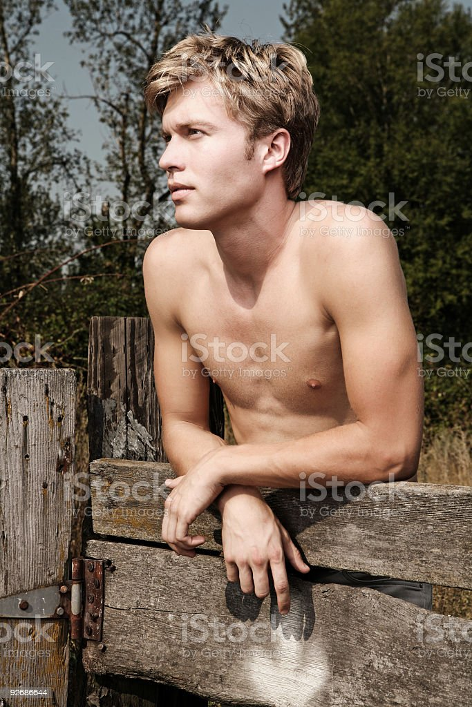 Shirtless Man Leans Out With Intrigued Expression. royalty-free stock photo