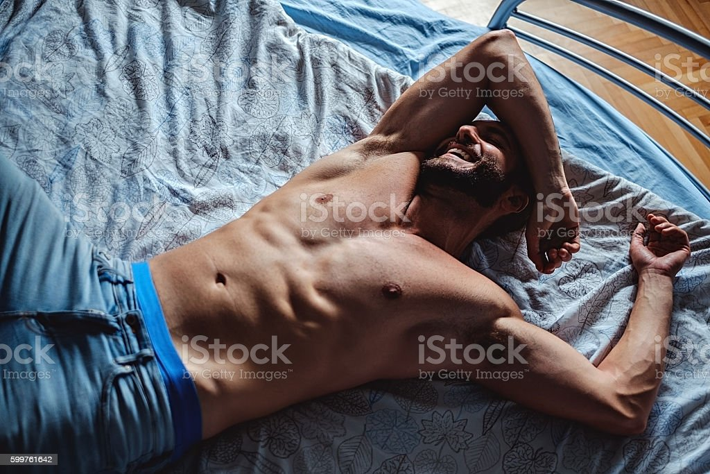 Shirtless man lying in the bad and smiling stock photo