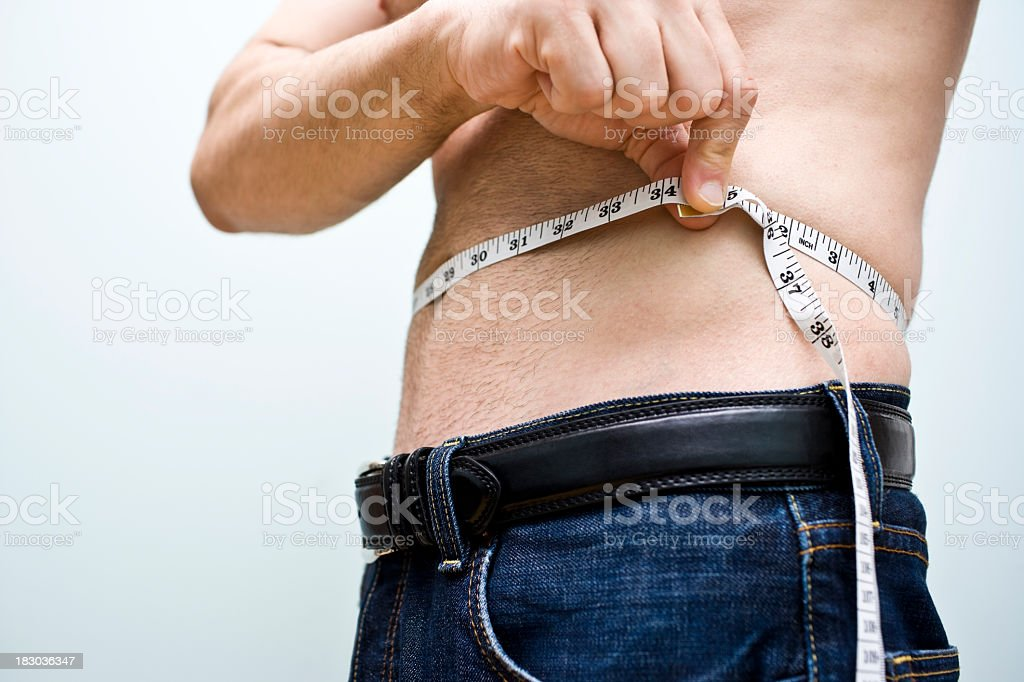 Shirtless man measuring his waist with a measuring tape stock photo