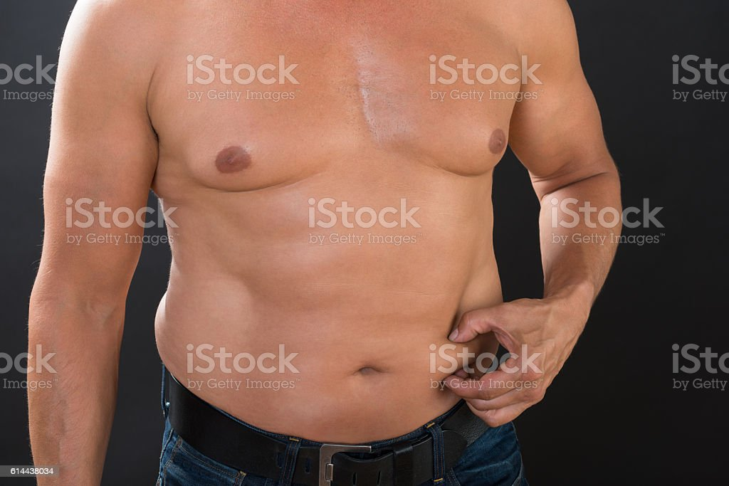 Shirtless Man Measuring Stomach Fat royalty-free stock photo