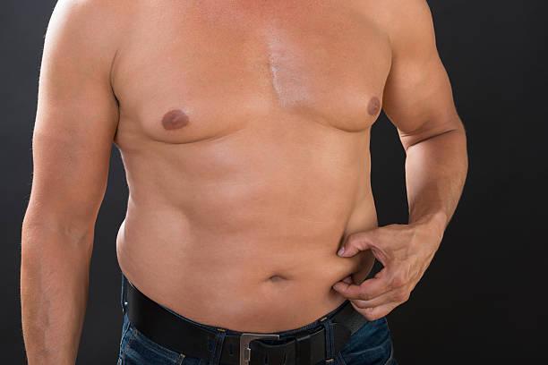 Shirtless Man Measuring Stomach Fat - foto de acervo