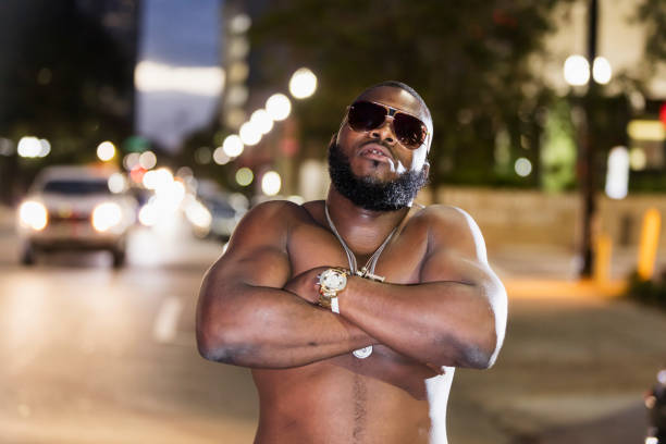 Shirtless man on city street at night, sunglasses, bling An African-American man with bling bling, standing on a city street at dusk, looking at the camera through sunglasses. He is a tough, shirtless, muscular man. gold teeth bling stock pictures, royalty-free photos & images