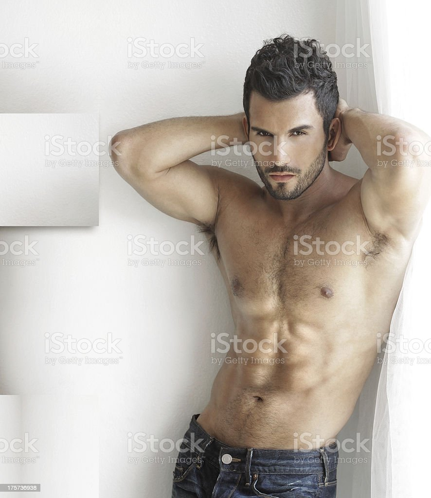 Shirtless man showing off abs with hands behind his head stock photo