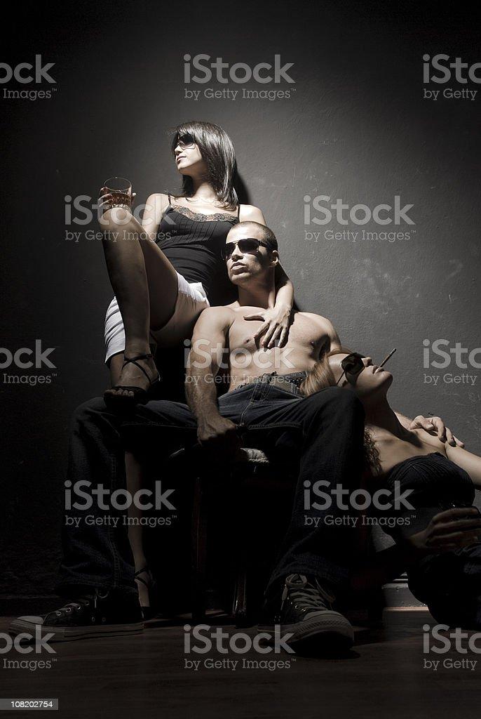 Shirtless Man Sitting Between Two Women royalty-free stock photo