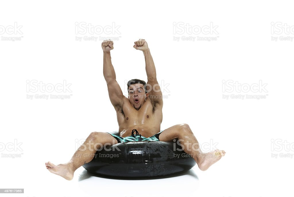 Shirtless man sitting on inner tube & cheering royalty-free stock photo
