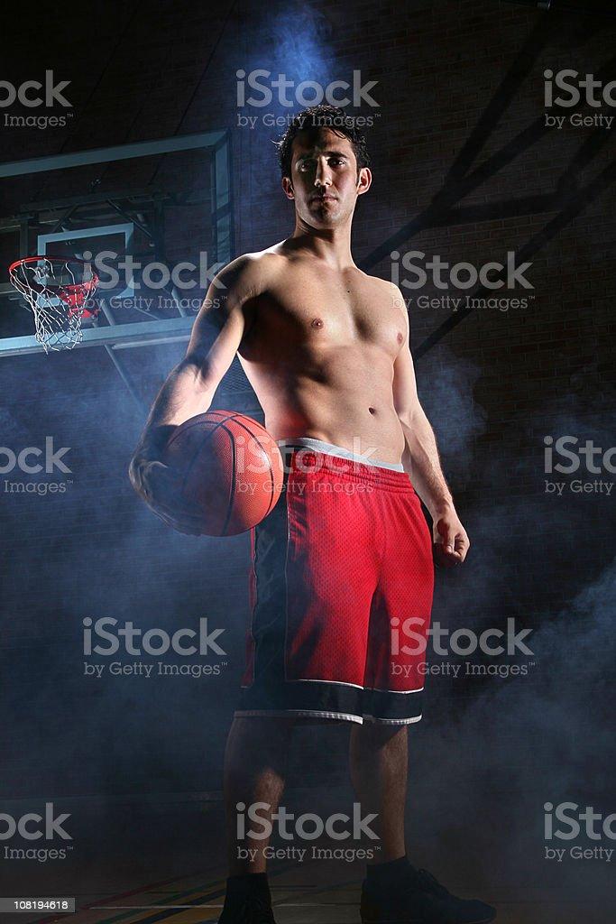 Shirtless Man Standing on Basketball Court, Low Key stock photo