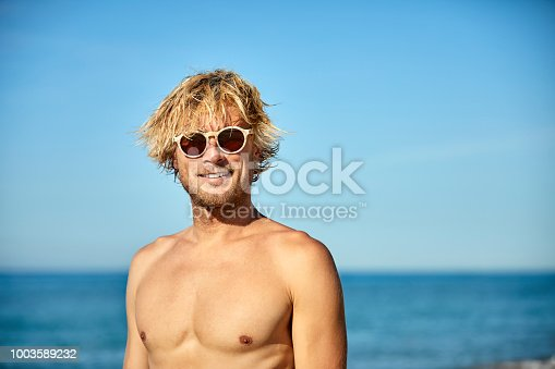 Portrait of shirtless man wearing sunglasses at beach. Handsome smiling male is standing against sky on sunny day. He is enjoying summer vacation.