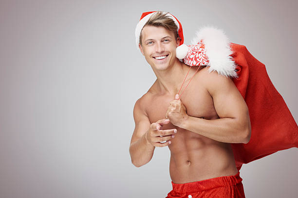 shirtless man with christms sack - naked santa claus stock pictures, royalty-free photos & images
