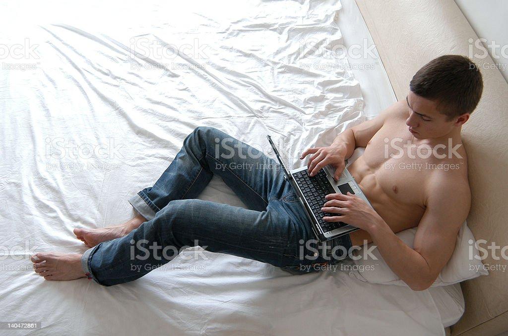 Shirtless Man Working on a Laptop royalty-free stock photo