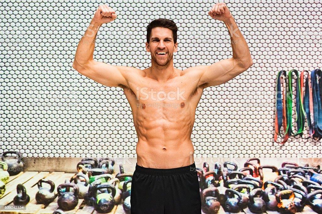 Shirtless muscular man cheering in gym royalty-free stock photo