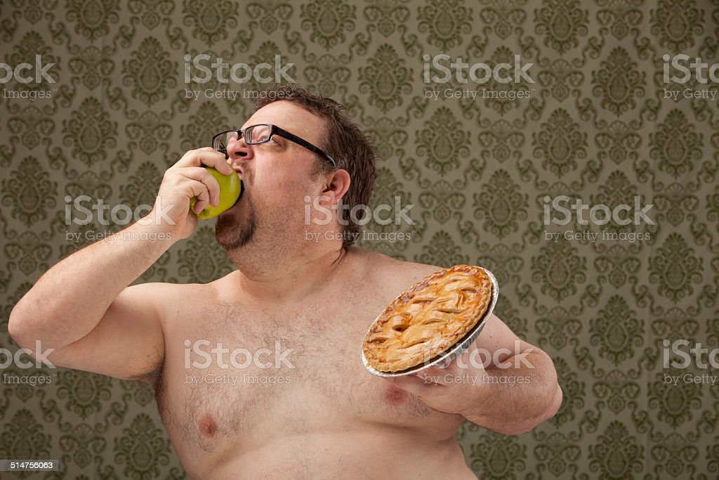 shirtless, overweight male eating apple and holding pie stock photo