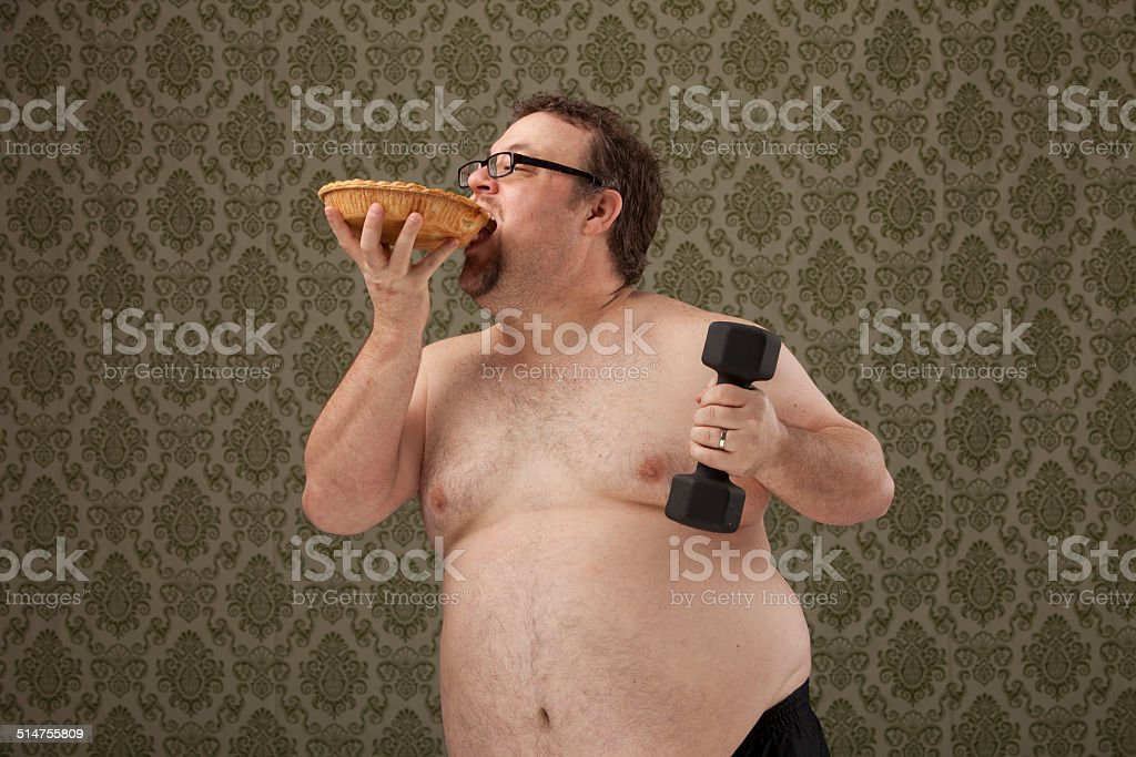 shirtless, overweight male lifting weights and holding pie stock photo