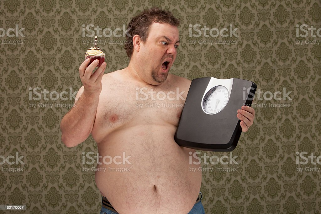 shirtless overweight male yelling at his scales while holding a stock photo