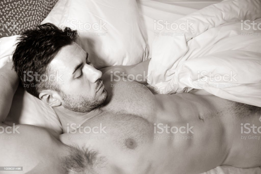 Shirtless sexy hunky man with beard and six pack abs lies naked in bed stock photo