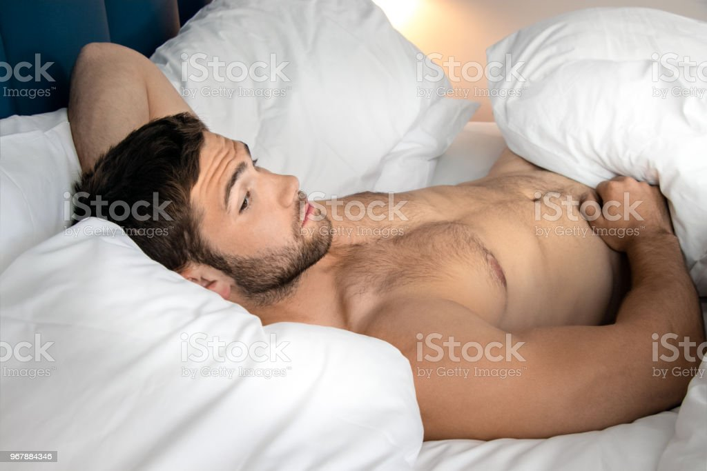 Shirtless sexy hunky man with beard lies naked in bed stock photo
