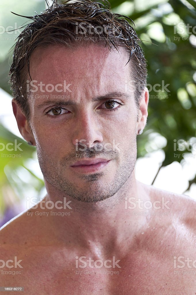 A shirtless, wet man staring intently at the camera.  royalty-free stock photo