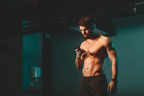 Shirtless young athletic man chooses music for workout in the gym stock photo