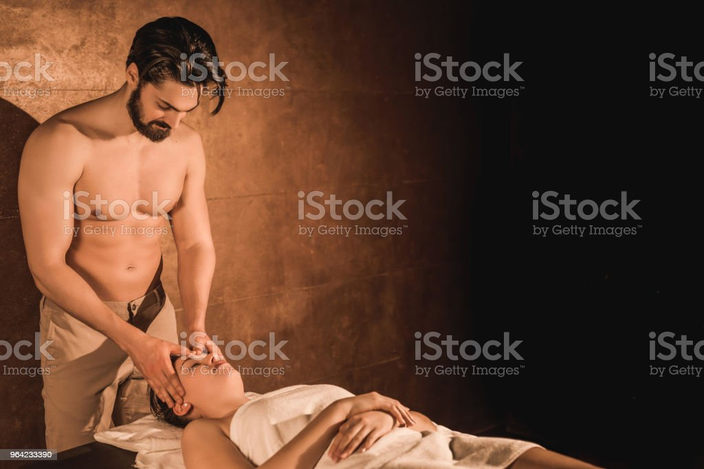 Shirtless young male massage therapist giving a head massage to...