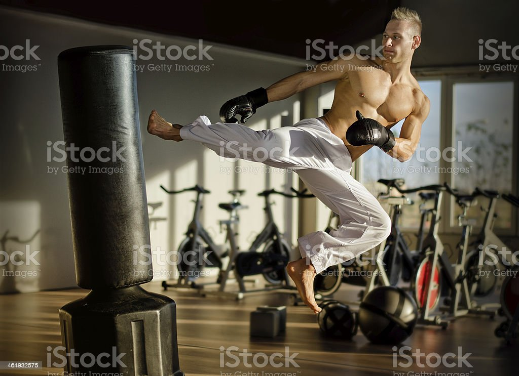 Shirtless young man doing flying kick royalty-free stock photo
