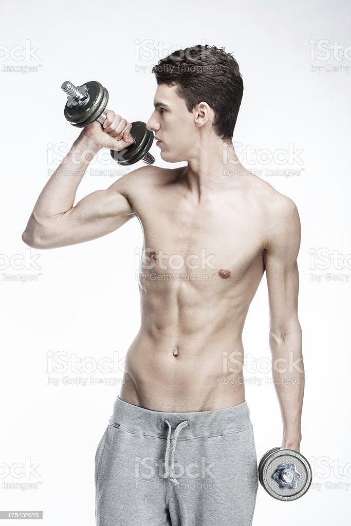shirtless young man holding dumbbells stock photo