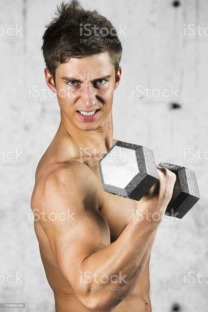 Shirtless young man lifting dumbbell royalty-free stock photo