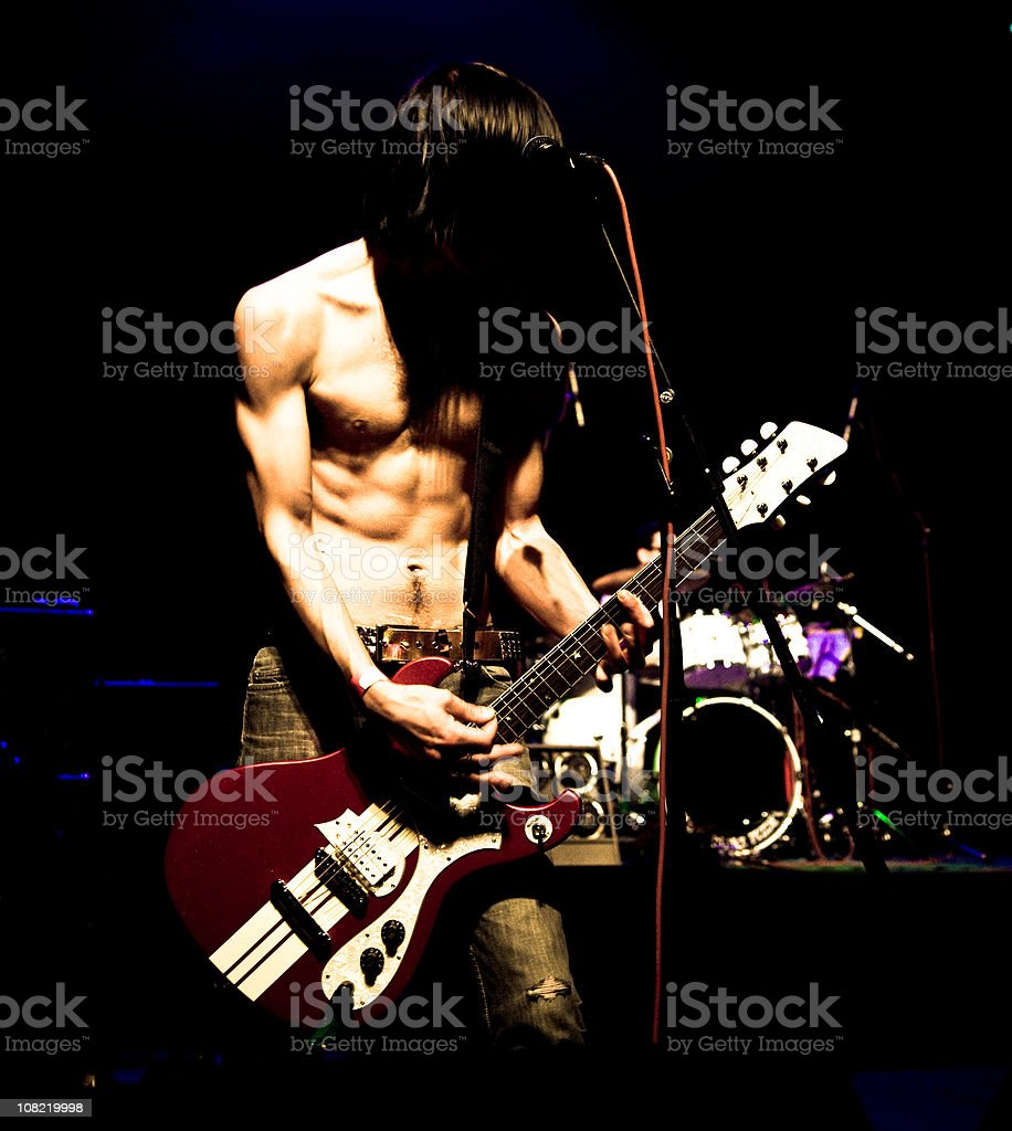 Shirtless Young Man Playing Guitar on Stage at Concert royalty-free stock photo