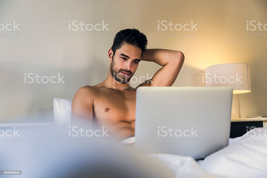 Shirtless young man using laptop in bed - Foto stock royalty-free di 20-24 anni