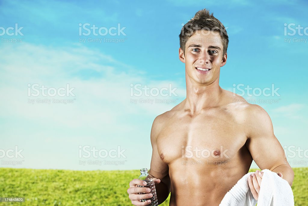 Shirtless young man with water bottle and towel royalty-free stock photo