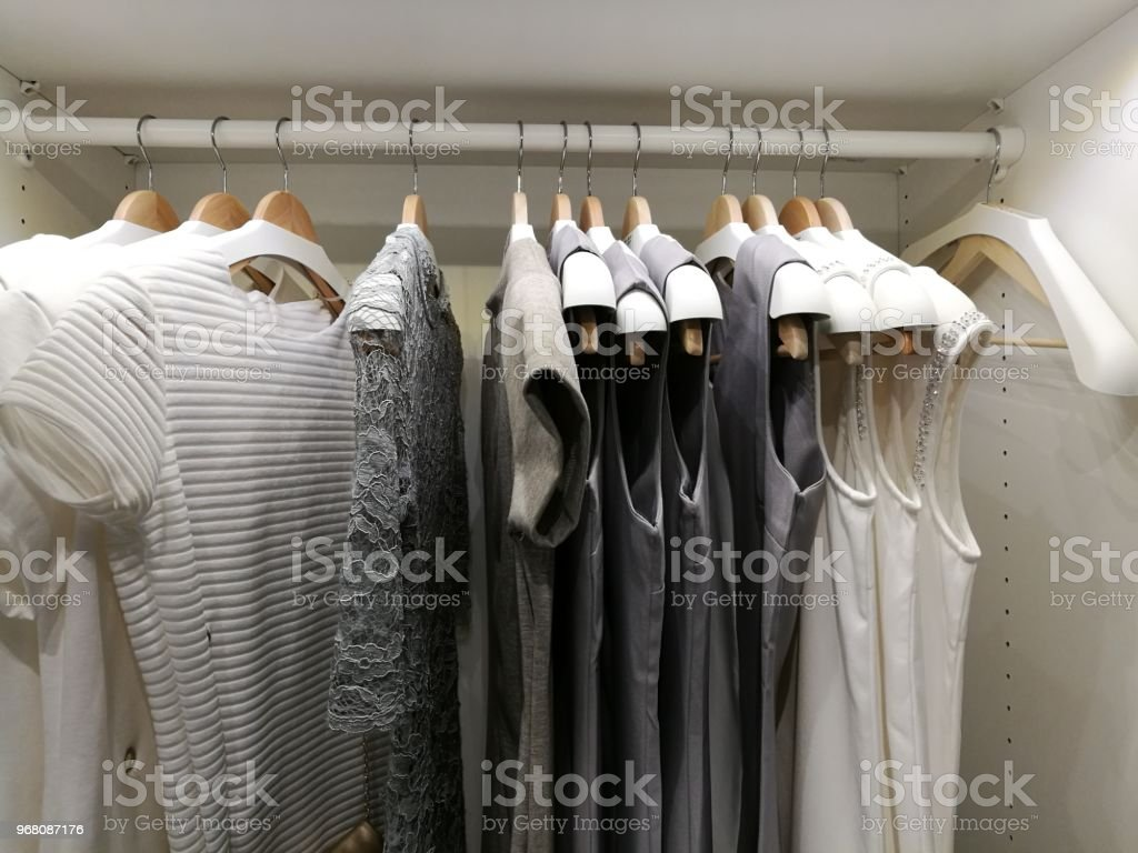 Shirts hanging on rack hang line in built-in cupboard.A row of...