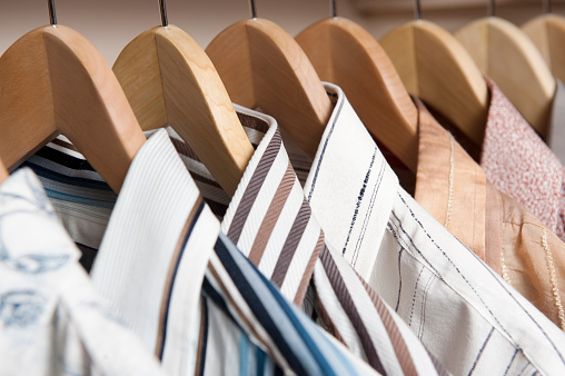 Men's dress shirts on wooden hangers.
