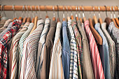 A variety of shirts hanging on a wooden clothes rack.