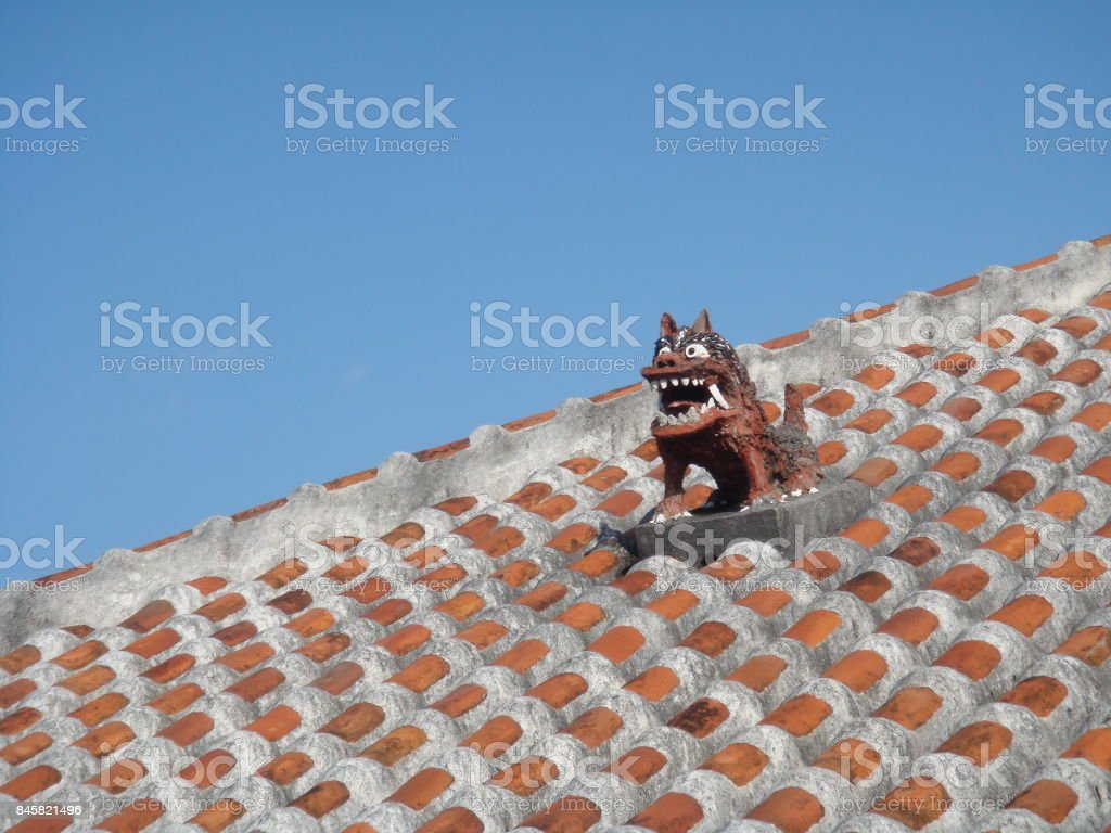 Shisa lion dog guardian on a traditional tile roof in Okinawa, Japan stock photo