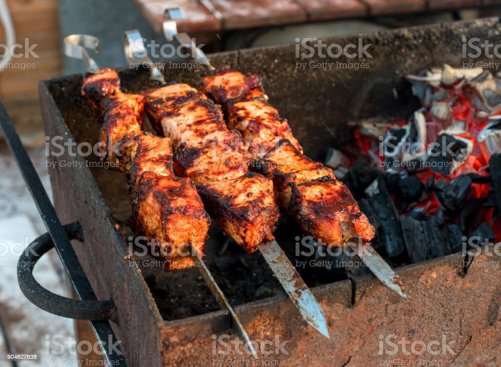Shish kebab is fried on a brazier. The shish kebab is strung on the skewer. Hot coals glow red. stock photo
