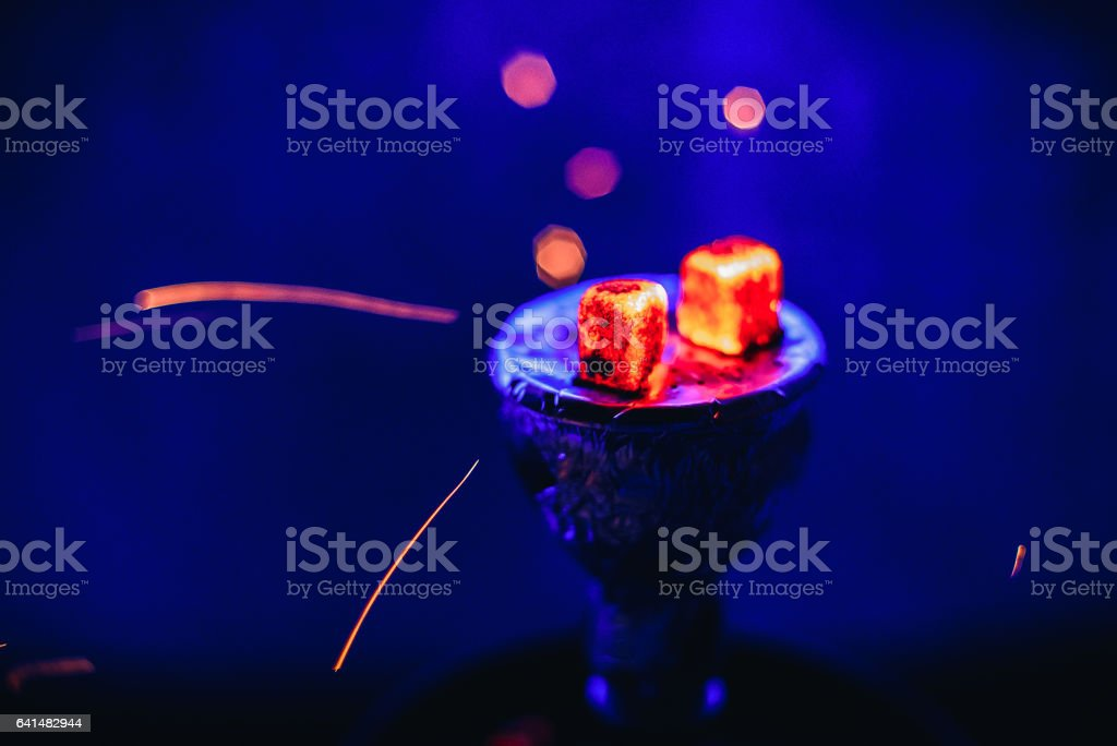 Shisha hookah with glowing red embers and flying sparks in bowl on blue background stock photo