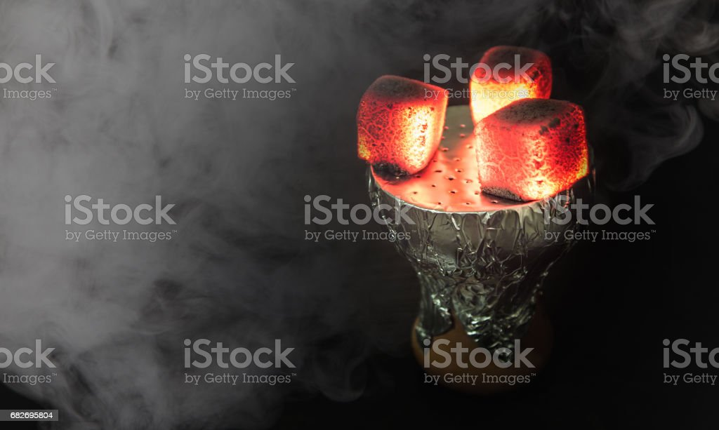 Shisha hookah with red hot coals. Smoke from breathe. stock photo