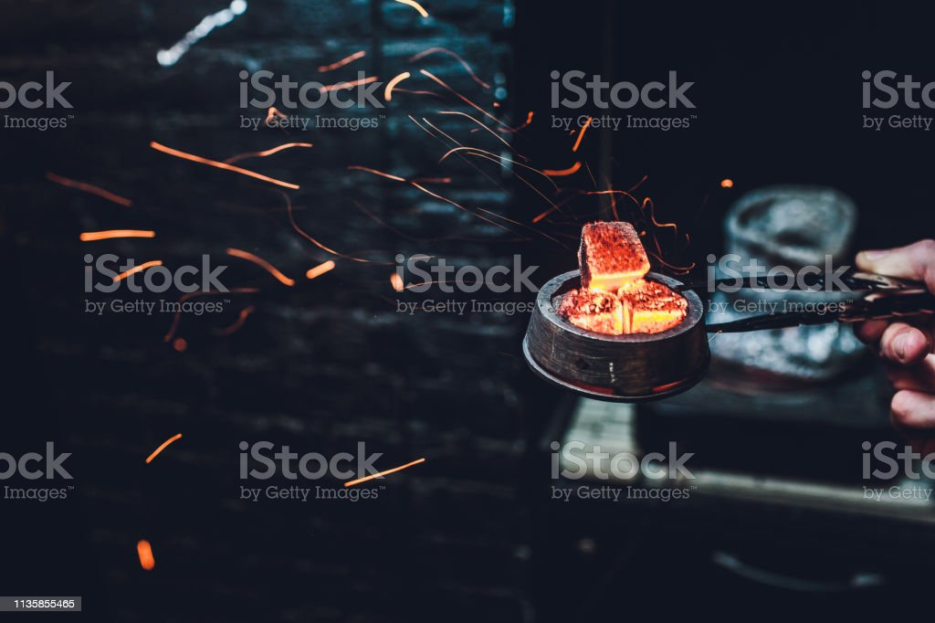 Shisha hookah with red hot coals. Sparks from breathe. Modern hookah...