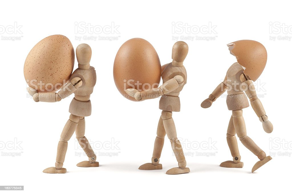 Shit happens - wooden mannequins carrying eggs royalty-free stock photo