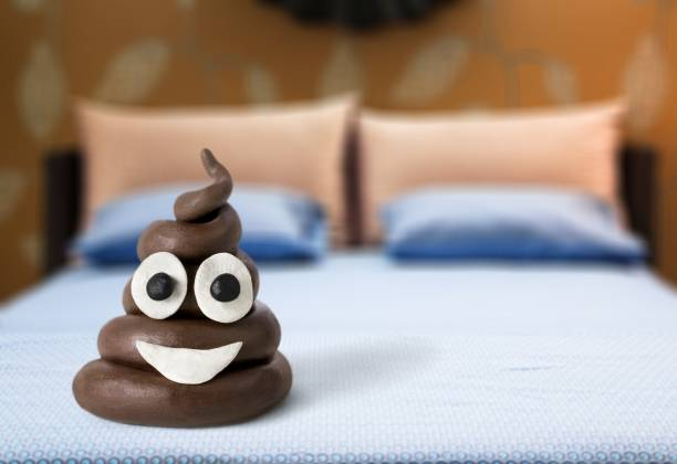 Shit. Poop emoticon on bed  background. poop stock pictures, royalty-free photos & images