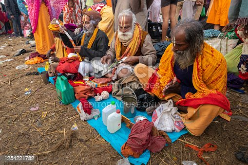Shiva devotees (recognised by the marks on their foreheads), sitting on the floor, with the holy water recently collected, and burning incense. They are preparing for some prayers, before they leave the bathing ghat.Photo taken during Kumbh Mela 2019 in Prayagraj (Allahabad), India.  Kumbh Mela or Kumbha Mela is a major pilgrimage and festival in Hinduism, and probably the greatest religious festival in the World. It is celebrated in a cycle of approximately 12 years at four river-bank pilgrimage sites: the Allahabad (Ganges-Yamuna Sarasvati rivers confluence), Haridwar (Ganges), Nashik (Godavari), and Ujjain (Shipra). The festival is marked by a ritual dip in the waters, but it is also a celebration of community commerce with numerous fairs, education, religious discourses by saints, mass feedings of monks or the poor, and entertainment spectacles. Pilgrims believe that bathing in these rivers is a means to cleanse them of their sins and favour a better next incarnation.