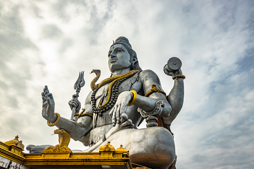 shiva statue isolated at murdeshwar temple close up shots from unique low angle image is take at murdeshwar karnataka india at early morning. it is one of the tallest shiva statue in the world.