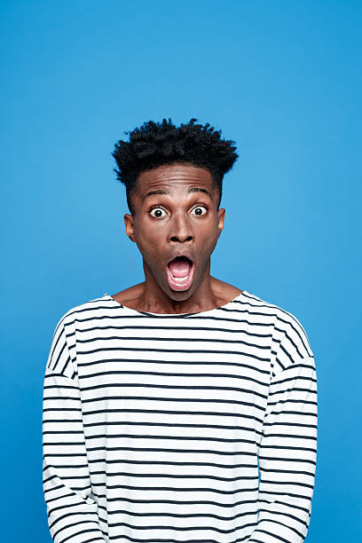 Shock, Afro american staring at camera with mouth open Studio portrait of afro american young man wearing striped top staring at the camera with mouth open. Studio portrait, blue background. gasping stock pictures, royalty-free photos & images