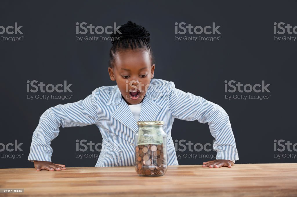 Shock businesswoman looking at coins in glass jar stock photo