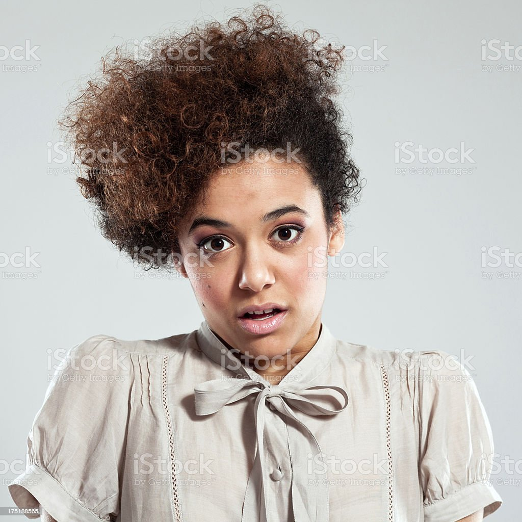 Shock Portrait of shocked teenaged afro girl looking at the camera . Studio shot, grey background. 18-19 Years Stock Photo